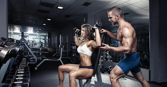 Фитнес инструктор и девушка с гантелями