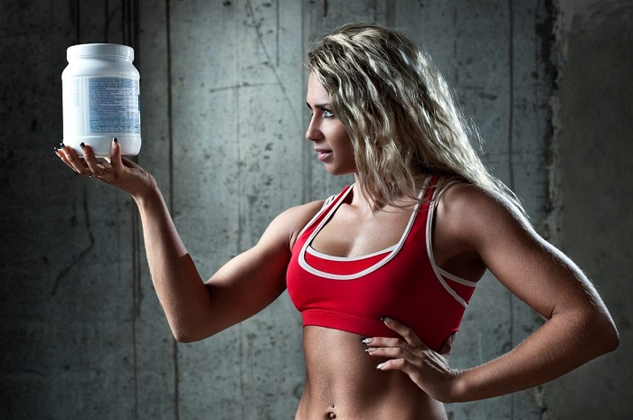 Девушка, спортсменка, банка спортивного питания