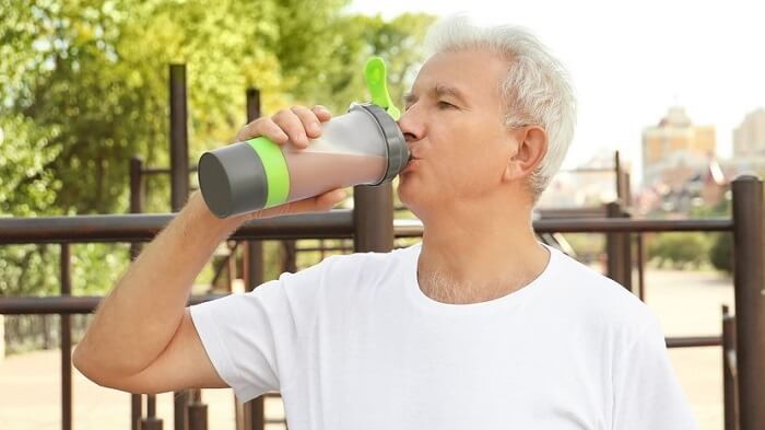 Мужчина в возрасте с протеиновым коктейлем
