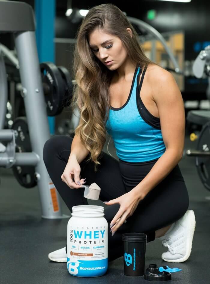 Девушка спортсменка. банка с протеином
