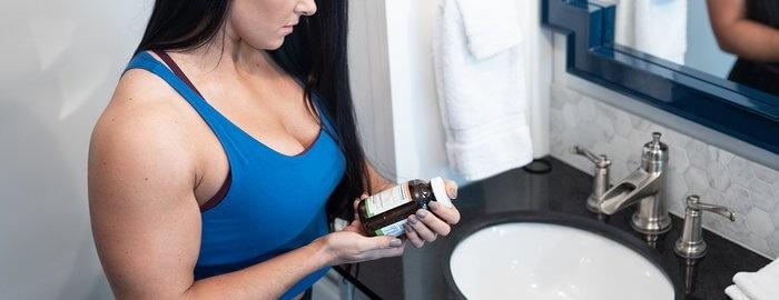 Девушка с банкой витаминов в ванной