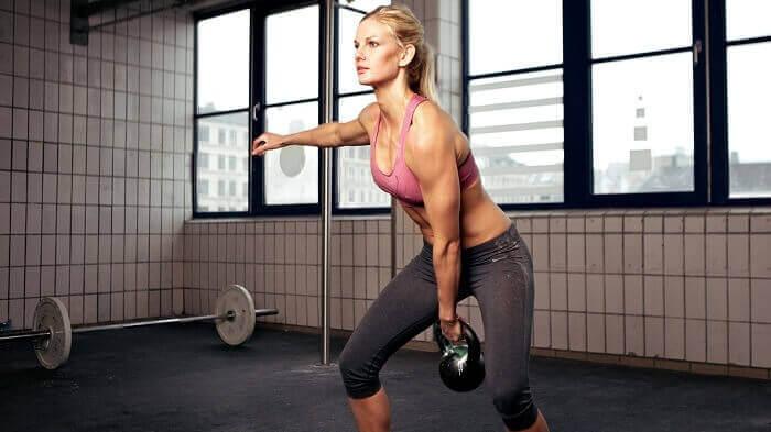 Девушка тренируется с гирей