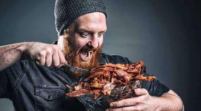 Мужик ест мясо