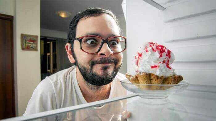 Мужик жадно смотрит на пирожное
